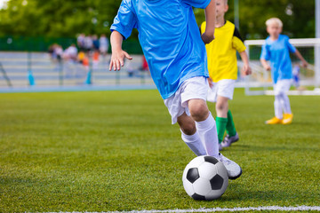 Training and football match between youth soccer teams. Young boys playing soccer game. Competition between players running kicking soccer ball. Game of football tournament for kids. Sport background.