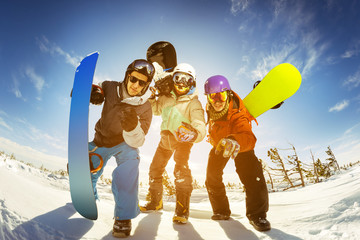 Snowboarders posing on blue sky backdrop in mountains