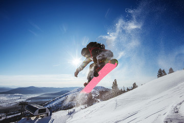 Snowboarder jumps on blue sky backdrop in mountains trick Wall mural
