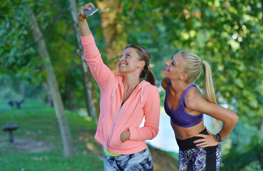 Shot of two females taking selfie during a quick break while out for a trail run using phone