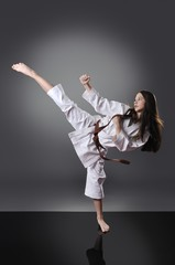 Beautiful young brown belt female karate doing kick on the gray background