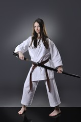 Beautiful young brown belt female karate posing with sword on the gray background