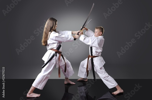 Male and female young karate fighting with swords on the gray ba