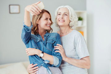 Positive delighted woman and her mother making selfies
