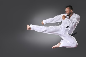 Handsome young black belt male karate doing kick on the gray bac