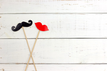 Paper heart shape fake mustaches in sticks in front of wooden white background. Wedding concept.