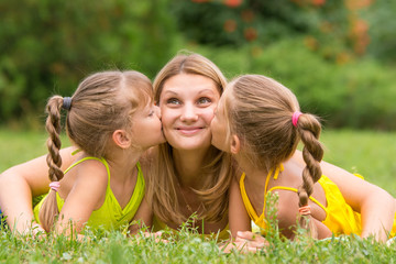 Two daughters kissing mother lying on the grass on a picnic, Mother looked up fun