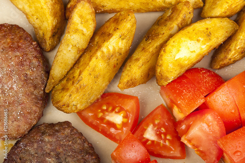 """Beef burgers with potato wedges and fresh tomato's"""" Imagens e fotos ..."""