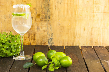 Lemonade in glass and green lemon on wooden background.Drink for health.Close up.