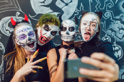 Three girls and a guy going on Halloween, grimace  make selfie