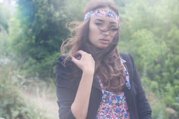 beautiful young woman posing outdoors during a fashion shooting. Special patches of light