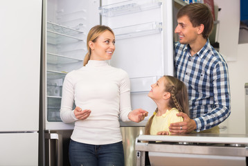 Smiling family with kid choosing refrigerator
