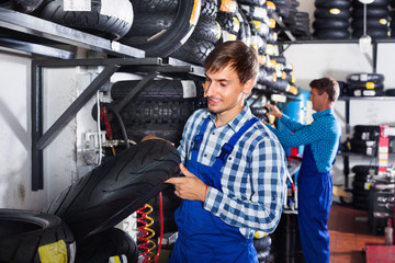 Portrait of mechanic working with bike tires in workshop