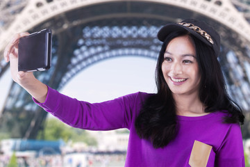 Beautiful girl takes selfie at Eiffel Tower