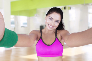 Healthy woman makes selfie photo at gym