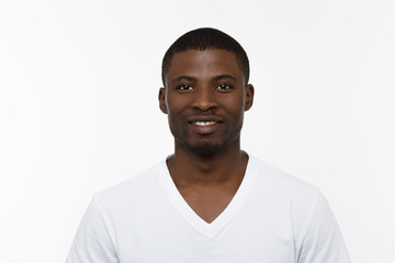 Portrait of African man smiling isolated on white background in studio. Handsome man in white T-shirt posing for photographer.