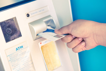 female hand inserting ATM card into bank machine to withdraw mon