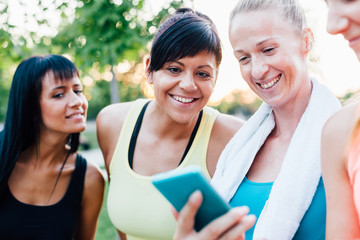 Sports women looking at fitness result on mobile phone