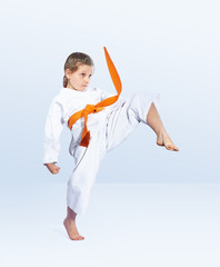 Karateka girl beats a kick leg forward