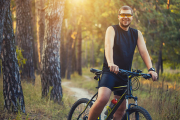 man cyclist rides forest paths