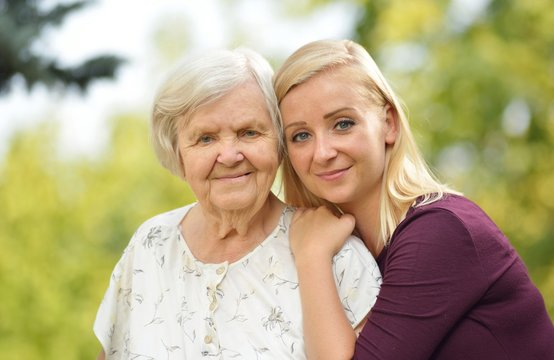 Grandmother and granddaughter. Young woman carefully takes care