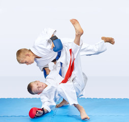 With a blue belt sportsman are throwing athlete with a red belt