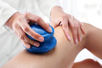 Masaż uda bańką chińską. Kosmetyczka masuje uda kobiety gumowymi bańkami do masażu.