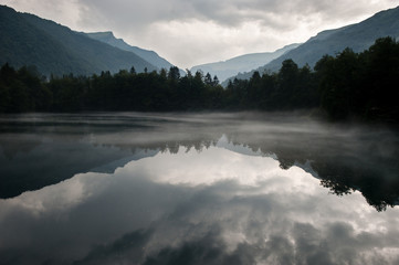 Obraz lake in the mountains covered in mist - fototapety do salonu