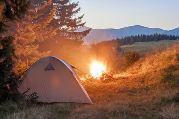 Hikers tent in mountains at evening with a bonfire with sparkles