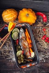 fish on the baking dish with cherry tomatoes, orange, garlic, on