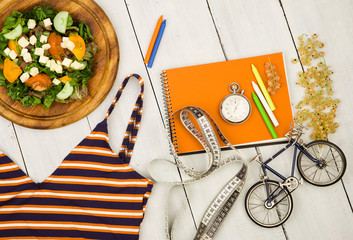 bicycle model, swimsuit, salad of fresh vegetables, orange notepad, stopwatch and tape measure on a white wooden table
