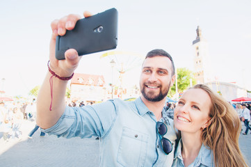 Catching the bright life moments. Beautiful young loving couple taking selfie with smart phone and smiling while traveling by Europe.