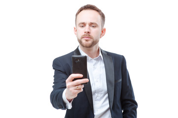 Taking photo with smartpnone. Confident young businessman in suit using mobile phone. Isolated on white.