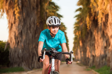 Portrait of young female cyclist riding bike on road with palms
