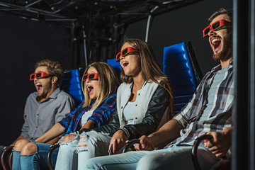four people laugh at cinema
