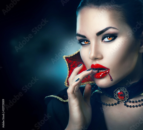 Halloween portrait. Beauty sexy vampire woman with dripping blood on her mouth