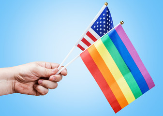 American and rainbow flag of the LGBT community in a hand