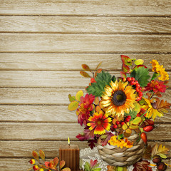 A bouquet of flowers, leaves and berries in a wicker basket on a wooden background