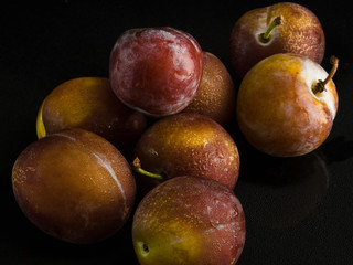 Ripe plums on a black background