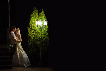 Bride and groom standing at night lantern. Taken with ISO, without further light. Wedding photography. On the bride long white dress, the groom is dressed in a suit.