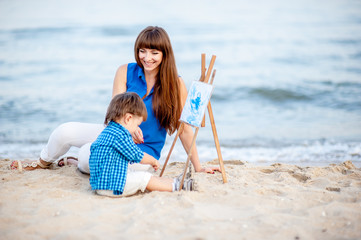 Woman and child in blue and white dress sit on the beach and draw on the easel