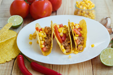 Three crispy tacos with chicken mince, tomatoes and corn served on a white plate together with other ingredients