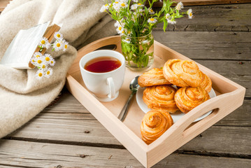 Cozy breakfast in spring or early autumn tea, freshly baked scones and bouquet of field's daisy and fascinating book. Copy space