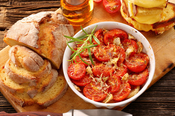 Baked tomatoes, corn bread and sandwiches with melted cheese
