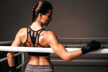 Young fitness beautiful brunette girl with boxing gloves on the ring