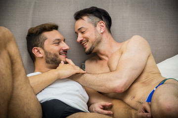 Handsome men lying on bed together while looking face to face with smile