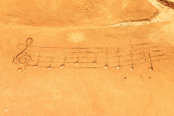 Drawn musical notes on a sandy beach