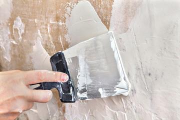 Painter puttied wall using a paint scraper, hand close-up.