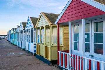 Row of colourful beach huts at sunset in Southwold, UK