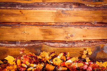 Autumn background with leaves, berries and vegetables at the wooden boards background. Copy space at the top.